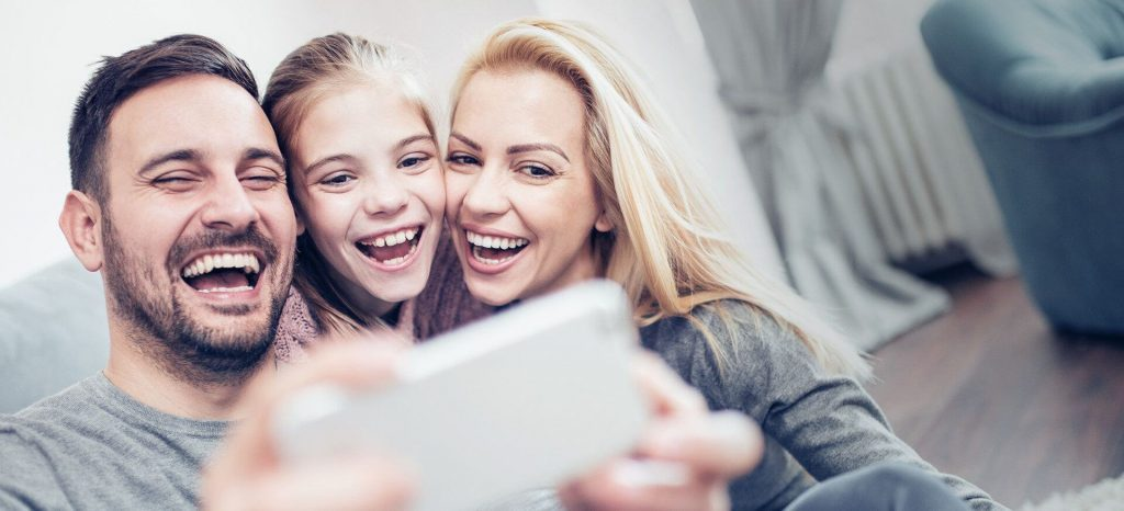 family smiling for a selfie
