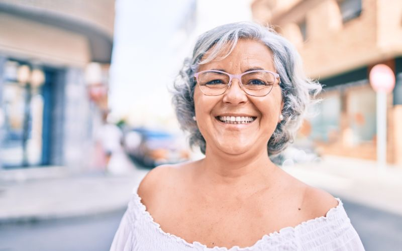 older woman with glasses smiling